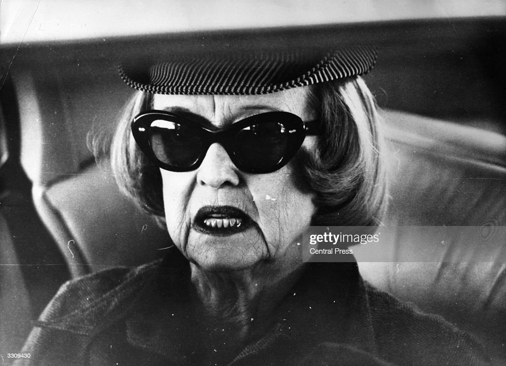 Bette Davis, the American actress, in the back of a car while visiting Perth, Australia, for a show at the Entertainment Centre.