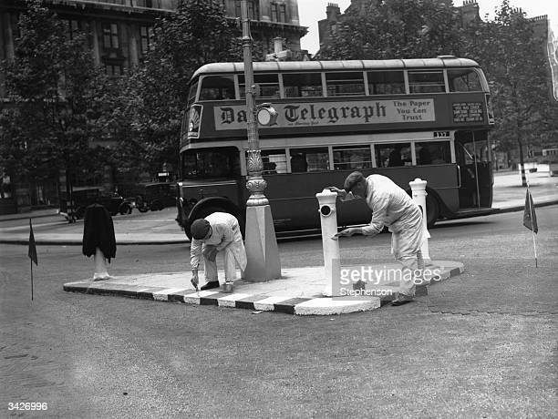 Painting street bollards white on a traffic island in Sloane Square London in preparation for a practice blackout prior to WW II