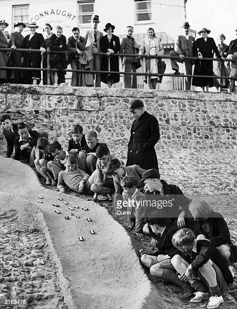 Youngsters on holiday amuse themselves racing toy cars on a sand track on Bognor Regis beach, Sussex.
