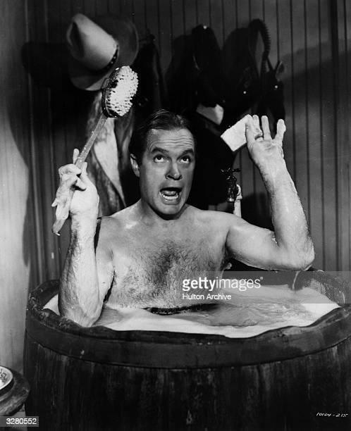 British born American comedian Bob Hope takes a bath