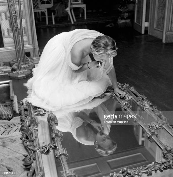 Judy Dunlop, a participant in the Holiday Girl Beauty Competition at the Royal Pavilion in Brighton, putting on her lipstick in the King's library....