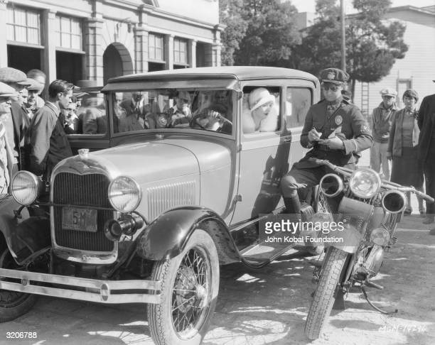 Director King Vidor pretends to charge actress Marion Davies with a driving offence during the filming of 'The Patsy'