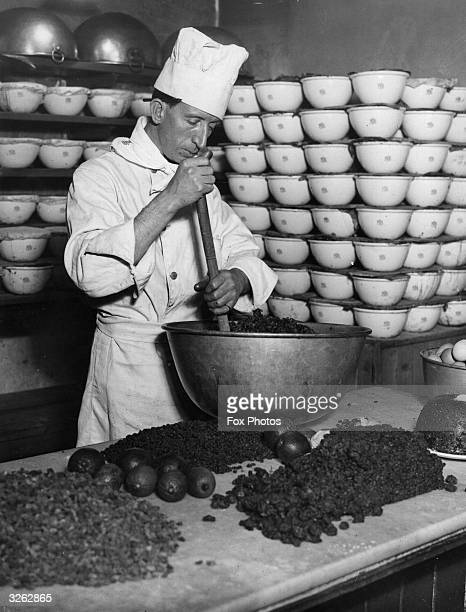 A chef stirring Christmas pudding mix in the kitchens at King's Cross station London for the thousands of puddings being made for the restaurant cars...
