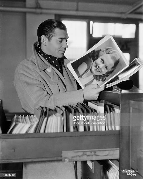 American actor Clark Gable admiring a photograph of actress Jean Harlow with whom he costarred in six films