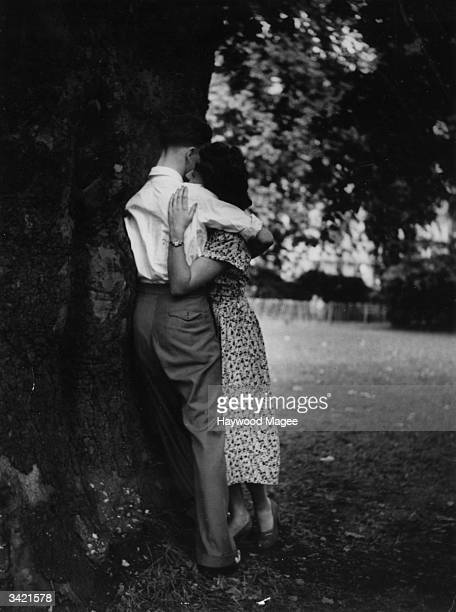 Young couple embracing on a spring evening, in a London park. Original Publication: Picture Post - 5407 - Sex And The Citizen - pub. 1951