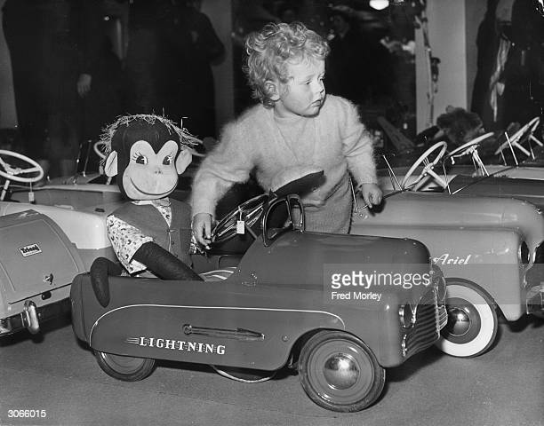 Madeleine Duke playing with a toy car and monkey driver at Harrods London