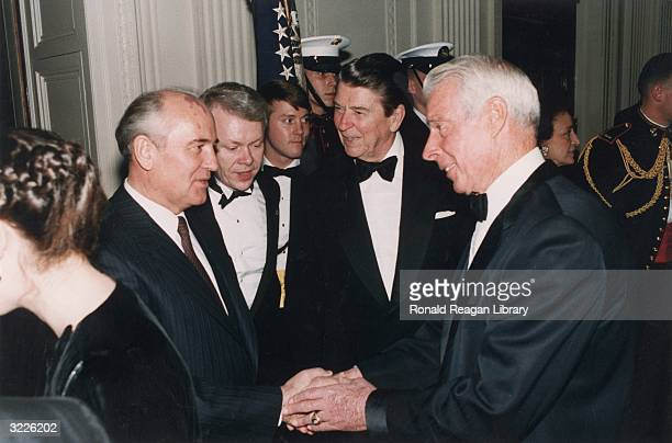 Soviet general secretary Mikhail Gorbachev shakes hands with former baseball player Joe DiMaggio as US president Ronald Reagan looks on during a...