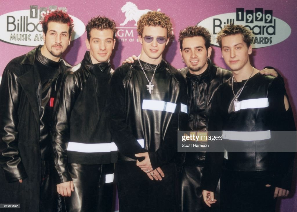 American pop group 'N Sync, wearing matching black leather outfits, posing in front of a wall of logos at the 1999 Billboard Music Awards, MGM Grand Hotel, Las Vegas, Nevada. L-R: Joey Fatone Jr., JC Chasez, Justin Timberlake, Chris Kirkpatrick, and Lance Bass.