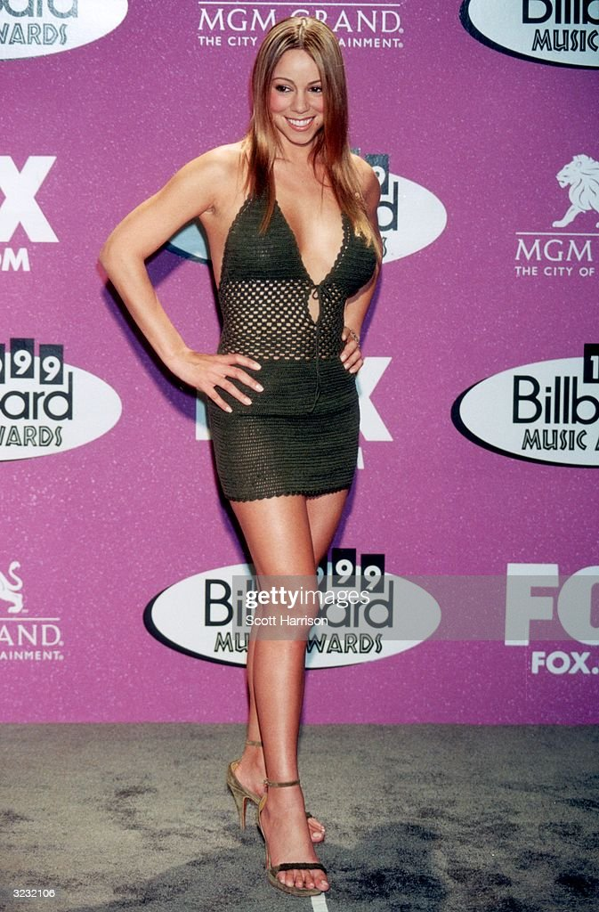 American pop singer Mariah Carey, wearing a black crocheted mini-dress, poses for photographers at the 1999 Billboard Music Awards, held at the MGM Grand Hotel and Casino in Las Vegas, Nevada. Carey won the Artist of the Decade award.
