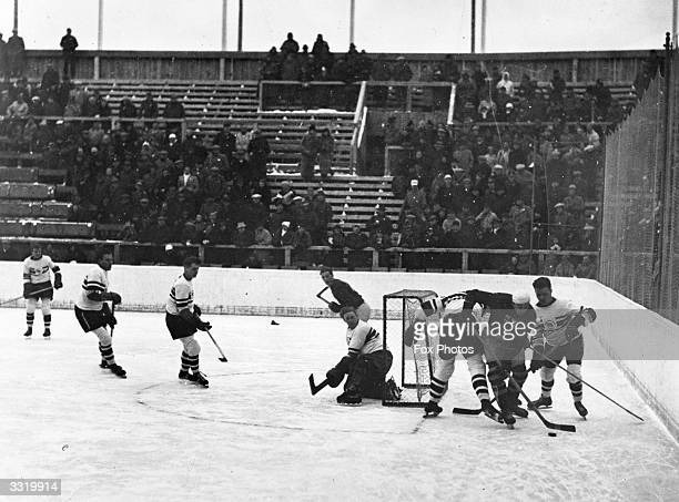 The British goal being attacked by Sweden during an ice hockey match at the Garmisch-Partenkirchen Winter Olympics, Bavaria, Germany. The British...