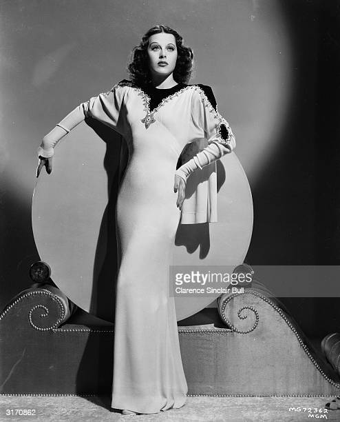Austrian born actress Hedy Lamarr leans against a circular backdrop wearing a long figure-hugging dress. She is starring as Georgi Gragore in 'I Take...