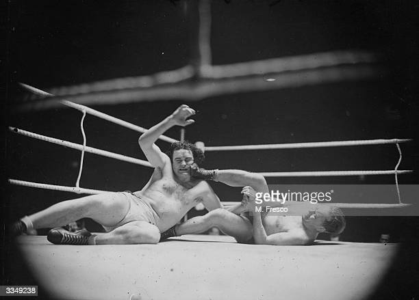 Estonian wrestler Bucht shoves his foot under Jack Doyle's chin during their international heavyweight contest at Harringay Arena London Doyle won...