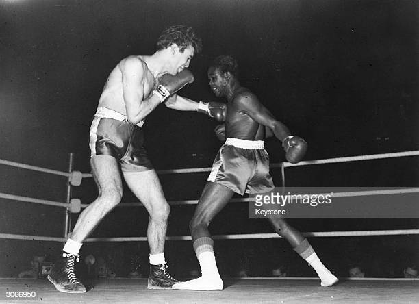 Kid Gavilan of Cuba aims a swinging right at Pete Waterman during their ten round welterweight contest which Waterman won on points causing a...