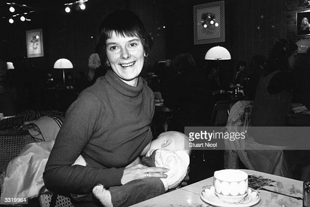 A woman breastfeeding her baby in the cafe of Harrod's department store Knightsbridge London