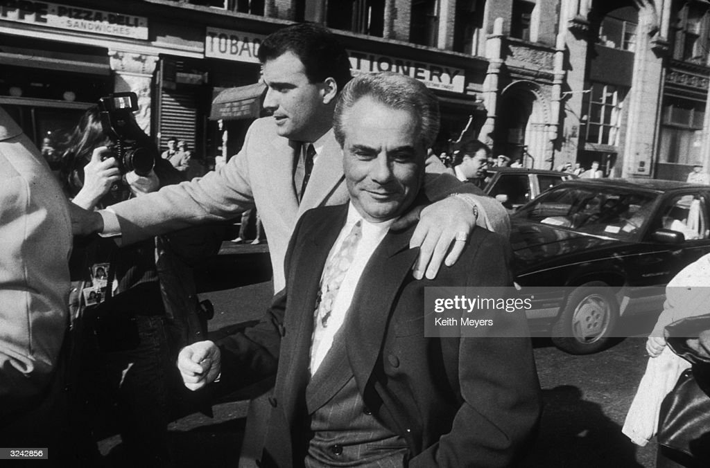 American reputed mafia boss John Gotti (1940 - 2002) leaves court with his lawyers during a recess in his trial for the jury's deliberation, New York City. A man has his arm on Gotti's shoulder.