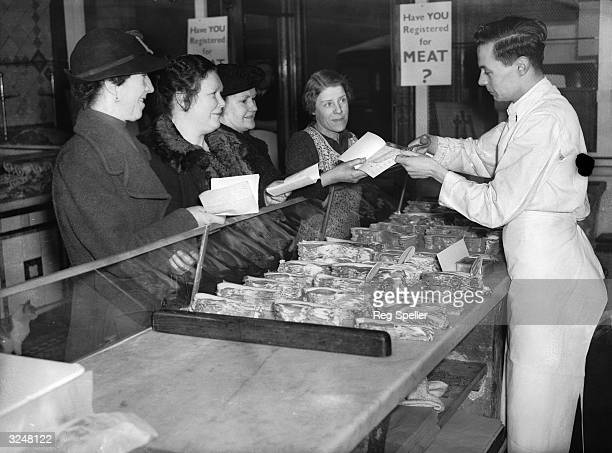 A shop assistant in a butcher's shop in south London cuts a coupon out of a customer's ration book on the first day of rationing in Britain