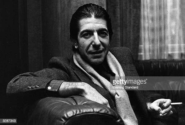 Solemn Canadian folk pop singersongwriter Leonard Cohen shares a joke and smokes a cigarette