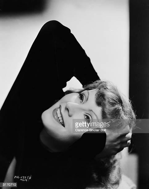 Swedish born actress Greta Garbo strikes an ecstatic pose.