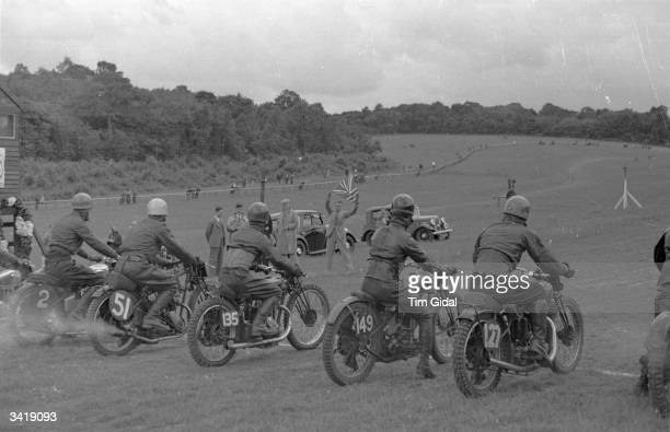 The official race starter waves the Union Jack to start the first event of the day at a grass track motorcycle race meeting Original Publication...