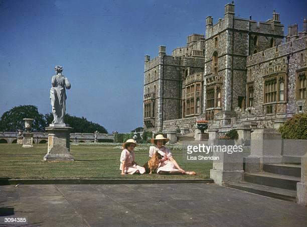 Princesses Elizabeth and Margaret Rose sunbathing outside Windsor Castle, Berkshire.