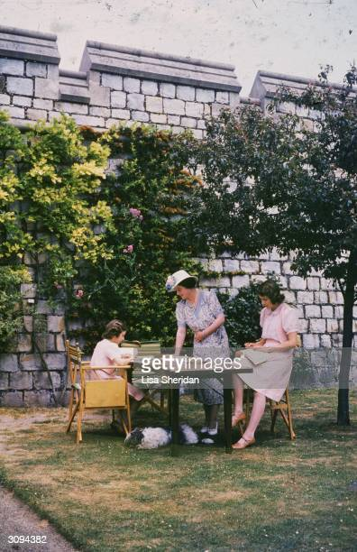 Queen Elizabeth, Queen Consort to King George VI with Princesses Elizabeth and Margaret Rose as they work at a desk in the grounds of Windsor Castle,...