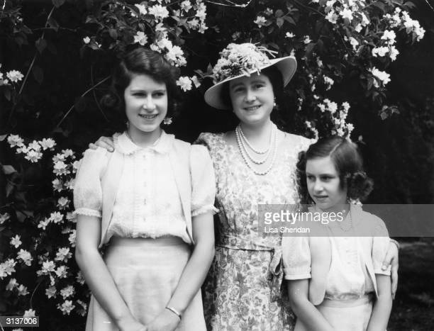 Queen Elizabeth with on the left her daughter Princess Elizabeth and on the right Princess Margaret in the garden at Windsor Castle during WW II