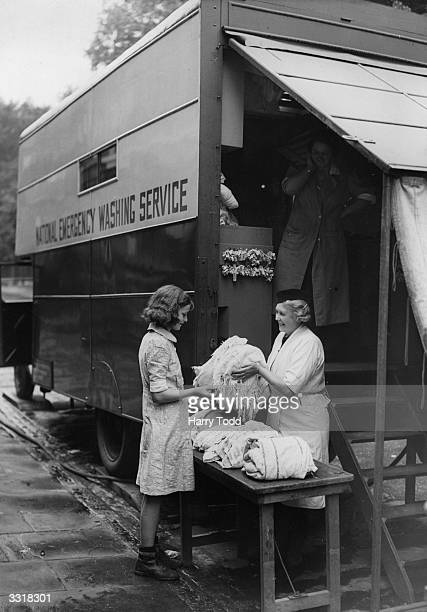 Girl getting her clothes washed at the National Emergency Washing Service under the supervision of the Women's Voluntary Service.