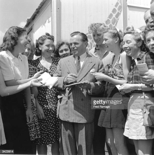 British holiday promoter and director of Butlin's holiday camps Billy Butlin surrounded by autograph hunters
