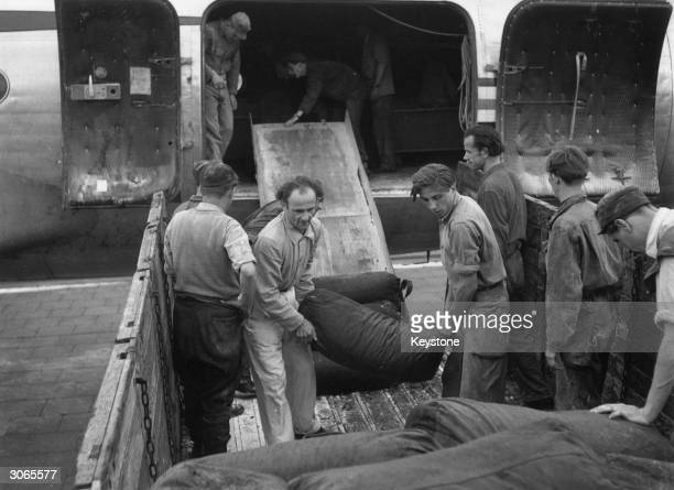 The first load of coal to be delivered by air arrives at Tempelhof Airport Berlin in a fleet of American Skymasters and is loaded onto lorries The...