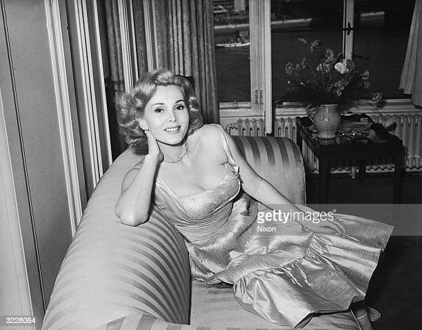 Hungarian actress Zsa Zsa Gabor lounges on a sofa in a ruched evening gown