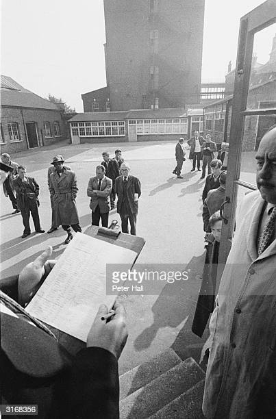 A roll is taken and details of inmates recorded in the yard of a reception centre for homeless men in Camberwell London
