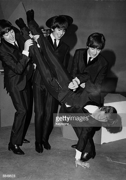 British pop band The Beatles in shiny suits at a BBC studio holding drummer Ringo Starr upside down to give him 'the bumps' the day after his 24th...