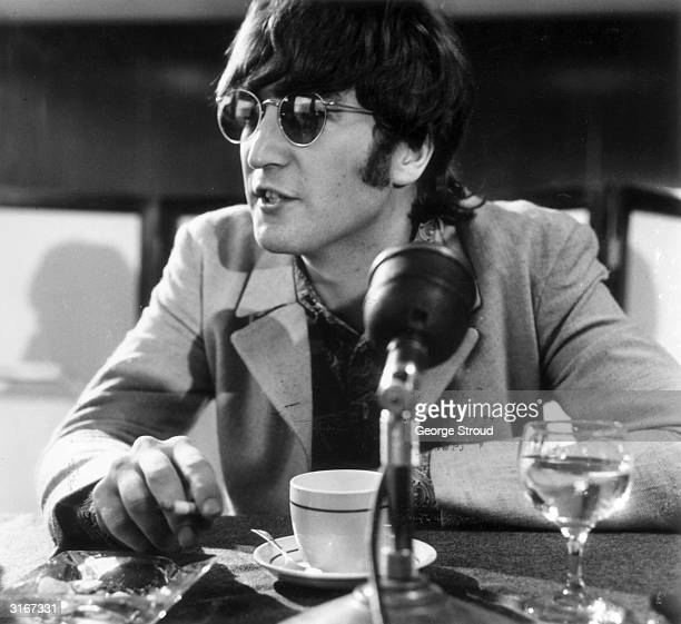 English pop star John Lennon at a press conference at London Airport after the Beatles' return from Manila