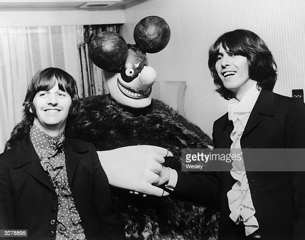 Beatles members Ringo Starr and George Harrison pose with a model of a Blue Meanie a character from the group's animated film 'Yellow Submarine' at a...