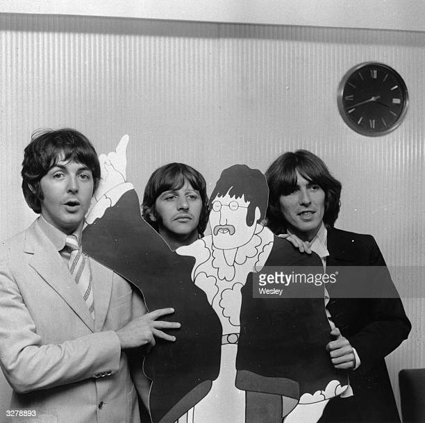 Beatles Paul McCartney, Ringo Starr and George Harrison pose with a cartoon cut-out of fellow Beatle John Lennon , at a press review of the group's...