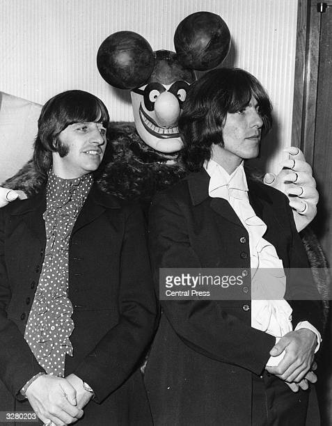 Two of The Beatles Ringo Starr and George Harrison posing with a model of a Blue Meanie a character from the group's animated film 'Yellow Submarine'...