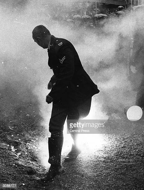 A policeman loses his hat as he runs from a smoke bomb during rioting by antiapartheid demonstrators at the Melbourne Olympic Park Australia during a...
