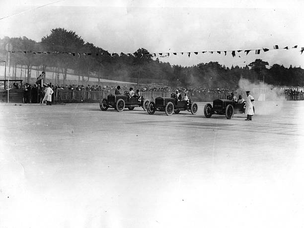 Three cars are lined up at the start of Brooklands...