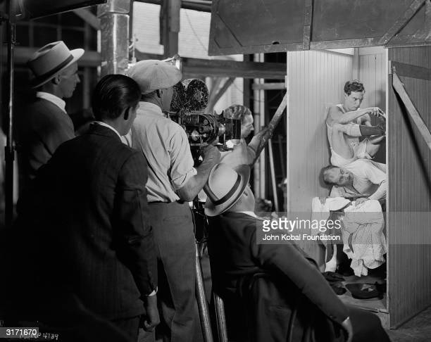 American comedian Buster Keaton gets tangled up with Edward Brophy while the film crew look on during the making of his latest film 'The Cameraman'