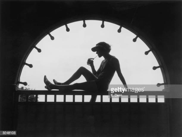 Young woman is silhouetted in an archway as she enjoys a cooling drink at Finchley Baths in north London.