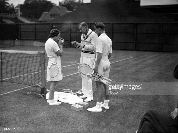 American tennis player Helen Jacobs lights a cigarette while fellow American Bill Tilden toys with the ball and Bunny Austin of Britain looks on The...