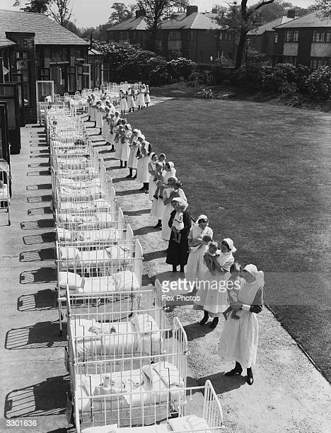Babies in a row of cots brought out for some sun by their nurses at the Duchess of York's Hospital for Babies at Burnage Manchester