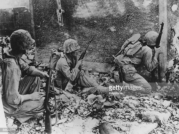 Group of 6th Division Marines take cover behind a wall during their fight amid the wrecked homes and rubble of Naha, capital city of the Japanese...
