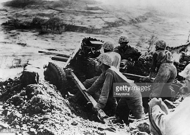 On the slope of a hill on Okinawa a marine gun crew take on Japanese pillboxes across the way.