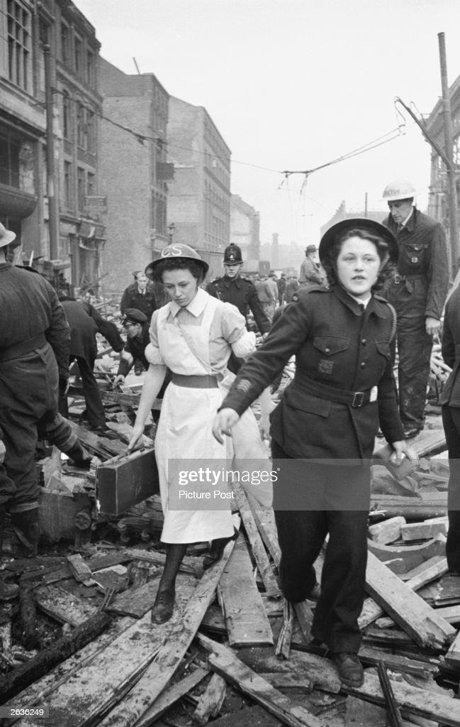 Rescue workers at the scene of a V-2 rocket attack on Farringdon Market in London during World War II. They are ambulance driver Jean Grover (right) and a nurse, who has the letters CS on her tin helmet. Original Publication: Picture Post - 1967 - One Story We Couldn't Tell - pub. 2nd October 1948