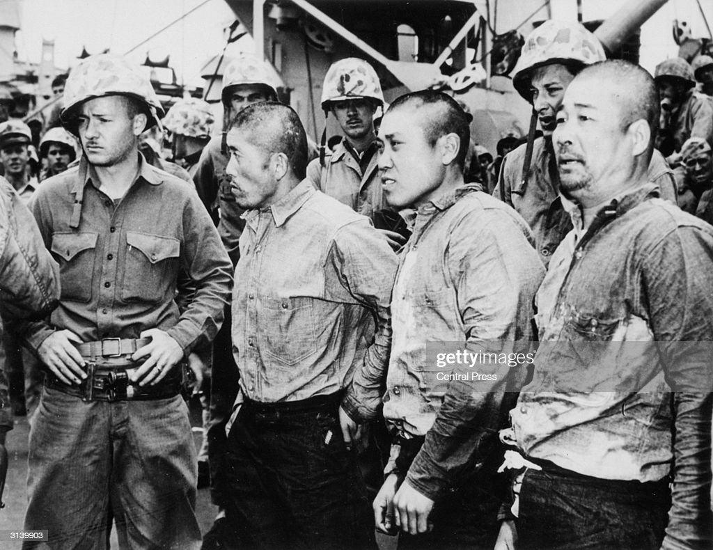 Three Japanese prisoners of war surrounded by American ...