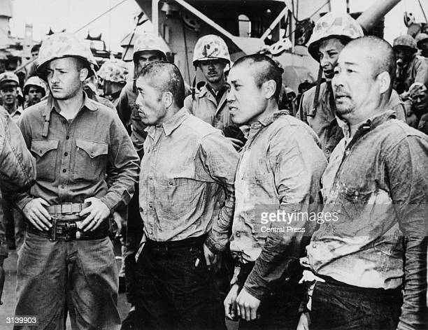 Three Japanese prisoners of war surrounded by American soldiers after they were captured during fighting on Iwo Jima.