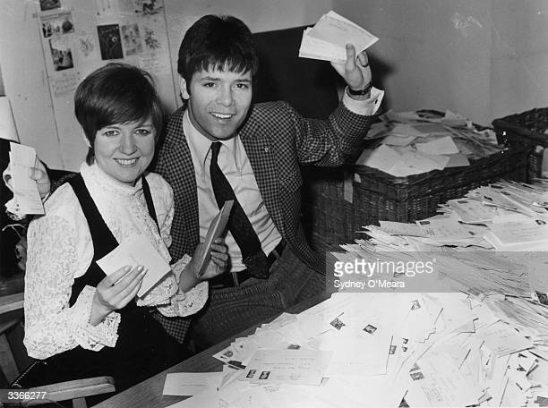 Pop stars Cilla Black and Cliff Richard counting the votes of television viewers for the 'Song For Europe' contest at Kensington House Richmond Way