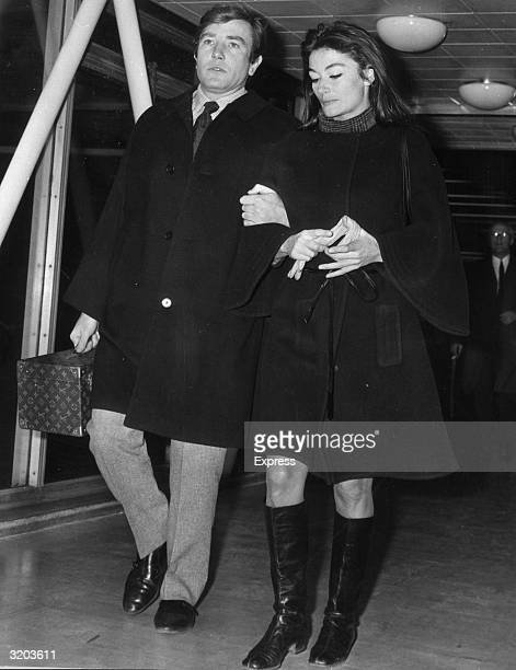 Fulllength image of British actor Albert Finney and his girlfriend French actor Anouk Aimee walking arminarm at London Airport England Finney carries...