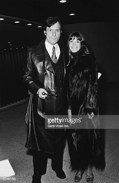 American magazine publisher Hugh Hefner holding a pipe and his companion American model and actor Barbi Benton attend a fight between Muhammad Ali...